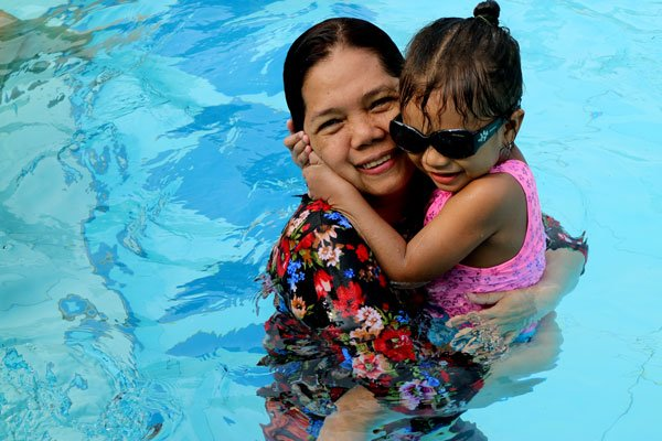 Child and grandmother enjoying a dip in the pool.