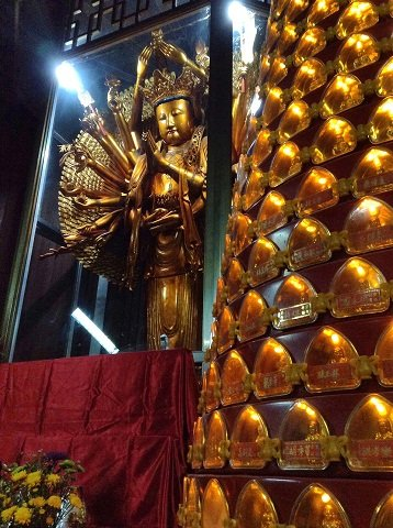 The golden statue of the Thousand-Armed Kuan Yina and a lighted pillar of miniature Buddhas.