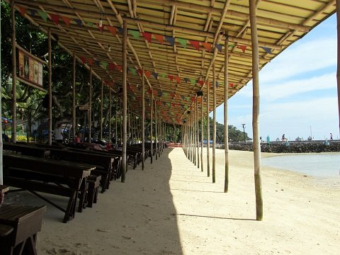 Wooden tables, benches and sun beds right by the shore.