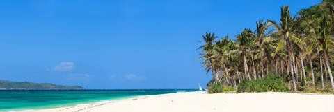 White sands and palm trees on Boracay Island beach in the Philippines