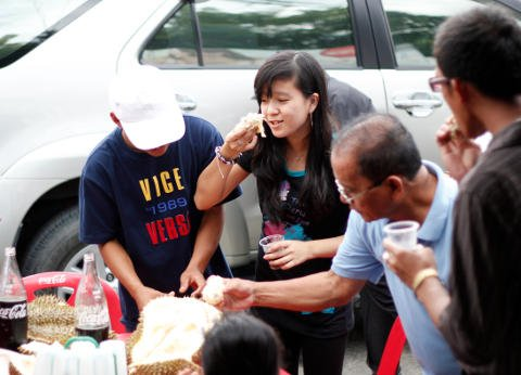 Group of Filipinos eating durian purchased from a street vendor