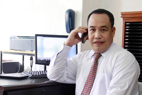 Filipino businessman on cell phone at office.