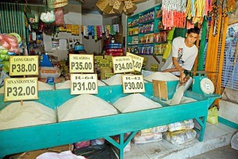 Filipino man selling a variety of long-grain rice.