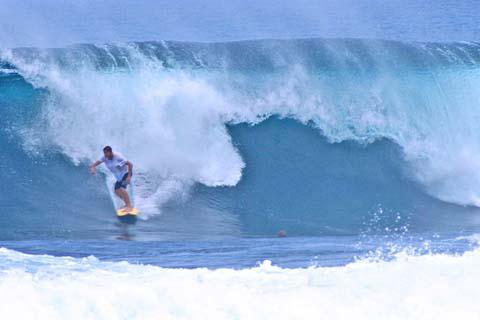 Surfer riding a wave at Siargao Island Philippines.