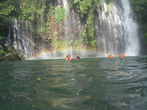 Adventurous travelers swim under the waterfall at Tinago Falls in the sleepy barangay of Ditucalan in the town Buru-un.